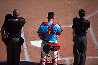 Spokane Indians catcher Isaias Quiroz (11) stands between umpires Bryan Van Vranken (left) and Emma Charlesworth-Seiler during the National Anthem before a Northwest League game against the Vancouver Canadians at Avista Stadium on September 2, 2018 in Spokane, Washington. The Spokane Indians defeated the Vancouver Canadians by a score of 3-1. (Zachary Lucy/Four Seam Images)