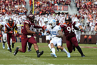 BLACKSBURG, VA - OCTOBER 19: Beau Corrales #15 of the University of North Carolina is tackled by TyJuan Garbutt #45 and Norell Pollard #96 of Virginia Tech during a game between North Carolina and Virginia Tech at Lane Stadium on October 19, 2019 in Blacksburg, Virginia.