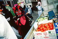 """Switzerland. Basel. Fasnacht Carnival. """"Clique""""  is a group of persons playing music in the streets during the three days of the Carnaval. The group passes-by a van delivering vegetables (tomatoes of Spain, salads,..) to a shop. © 1997 Didier Ruef"""