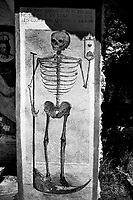 """Switzerland. Canton Ticino. Val (Valley) Verzasca. Brione. Religious memorial ion the roadside. Memento Mori. A human skeleton, a scythe and a sandglass. The words in Italian language: «Remember you should die. Everybody both rich and poor will appear before the judgment of God». A memento mori (Latin 'remember that you must die') is an artistic or symbolic reminder of the inevitability of death. The expression 'memento mori' developed with the growth of Christianity, which emphasized Heaven, Hell, and salvation of the soul in the afterlife. An hourglass (or sandglass, sand timer, sand clock or egg timer) is a device used to measure the passage of time. It comprises two glass bulbs connected vertically by a narrow neck that allows a regulated flow of a substance (historically sand) from the upper bulb to the lower one. Typically the upper and lower bulbs are symmetric so that the hourglass will measure the same duration regardless of orientation. Depictions of an hourglass as a symbol of the passage of time are found in art, especially on tombstones or other monuments, from antiquity to the present day. The form of a winged hourglass has been used as a literal depiction of the well-known Latin epitaph tempus fugit (""""time flies""""). 21.05.2020 © 2020 Didier Ruef"""