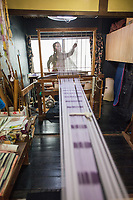Japan, Kyoto. This female master weaver uses a unique machine for kusari weaving, an old tradional craft to weave silk for kimonos. Usually this is a man's job, she learned from a traditonal master weaver, and she is the only woman doing this. Model released