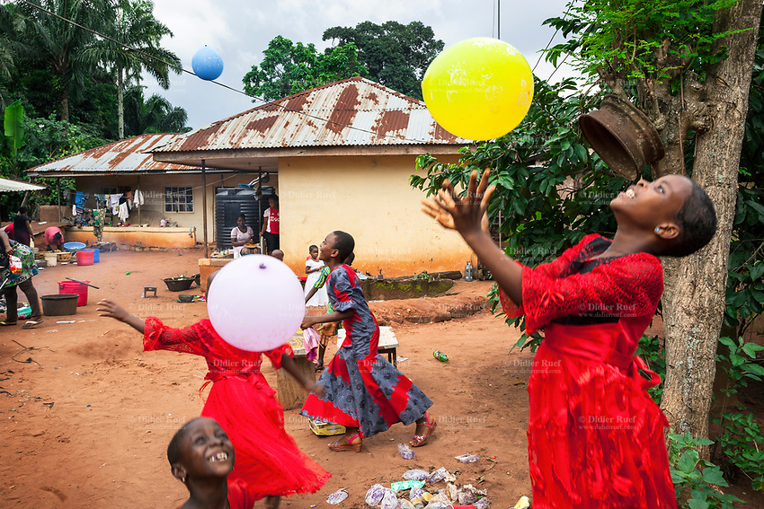 Nigeria. Enugu State. Awhun. Igbo traditional wedding ceremony. Cooking preparation before the party. Children play with colorful inflatable balloons in the house's courtyard . 29.06.19 © 2019 Didier Ruef