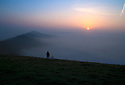 15/09/16 <br /> <br /> A walker stops with his dog on Mam Tor to admire the stunning dawn scene as the sun begins to burn through the mist clinging to valley above Castleton in the Derbyshire Peak District on what is forecast to be the third day in a row where UK temperatures will top 30 degrees. <br /> <br /> All Rights Reserved: F Stop Press Ltd. +44(0)1773 550665   www.fstoppress.com