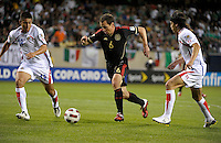 Mexico's Gerardo Torrado dribbles in between Costa Rica's Oscar Duarte (19) and Jose Salvatierra (4).  Mexico defeated Costa Rica 4-1 at the 2011 CONCACAF Gold Cup at Soldier Field in Chicago, IL on June 12, 2011.