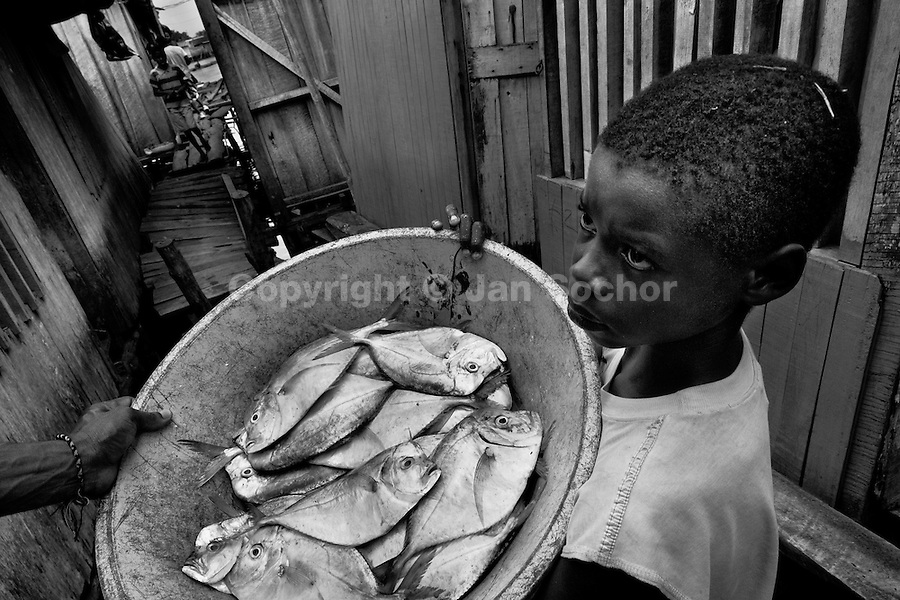 A displaced boy sells fish in the stilt house area in Tumaco, Nariño dept., Colombia, 11 June 2010. With nearly fifty years of armed conflict, Colombia has the highest number of civil war refugees in the world. During the last ten years of the civil war more than 3 million people have been forced to abandon their lands and to leave their homes due to the violence. Internally displaced people (IDPs) come from remote rural areas, where most of the clashes between leftist guerrillas FARC-ELN, right-wing paramilitary groups and government forces takes place. Displaced persons flee in a hurry, carrying just personal belongings, and thus they inevitably end up in large slums of the big cities, with no hope for the future.