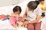 18 month old toddler girl with grandmother, playing with wooden peg shape sorter toy, grandmother steadying toy, 3 year old brother in background