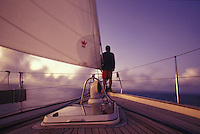 Man at bow of sailboat just after sunset, crossing the Pacific from Marquesas to Hawaii