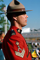 Canadian Mountie, Royal Canadian Mounted Police (RCMP) Officer wearing Traditional Red Surge Uniform and standing at Attention, Vancouver, BC, British Columbia, Canada (No Model Release Available)