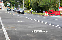 """BNPS.co.uk (01202) 558833. <br /> Pic: CorinMesser/BNPS<br /> <br /> Pictured: A cyclist in the road, alongside the 11'2"""" wide cycle lane. <br /> <br /> A cycle lane which is believed to be one of Britain's widest has been slammed by road users who are bemused by its size.<br /> <br /> Despite measuring over half as wide as the adjacent road, cyclists have still been spotted using the carriageway instead of the cycle lane.<br /> <br /> The cycle way is a whopping 11ft wide, 2ft wider than the vehicle lane which locals say is frequented by heavy goods and emergency vehicles.<br /> <br /> Residents on Wimborne Road West in Wimborne, Dorset, were exasperated when they woke one morning to the 'cycle highway' as it has been dubbed by the local council.<br /> <br /> It is part of a major £102 million scheme to make travel more sustainable and reduce congestion across the county but they argue it could have the opposite effect by obstructing traffic."""