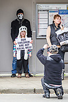 """© Joel Goodman - 07973 332324 . 03/03/2012 . Heywood , UK . A man holds a placard in front of a young girl that reads """" Our children are not halal meat """" as another man takes a photo of the two . The National Front hold a rally in protest against an alleged paedophile ring that had been operating in the area . There is currently (3rd March 2012) a case being tried at Liverpool Crown Court in relation to the allegations . Last Thursday (23rd February 2012) a protest organised in the town in relation to the same story resulted in Asian business being attacked by an angry mob . Photo credit : Joel Goodman"""