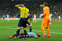 Alvaro Pereira of Uruguay is unconscious as the referee and Diego Godin call for medics