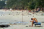 A foreign tourist hangs his head in sorrow as he sits alone on Patong Beach the day after the tsunami destroyed sections of Phuket Island, Thailand. On December 26, 2004, a major earthquake generated tsunamis that ravaged coastlines from Southeast Asia to Africa. Approximately 275,000 people were killed and tens of thousands were left homeless, making it one of the deadliest natural disasters in history.