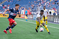 FOXBOROUGH, MA - MAY 16: Derrick Etienne Jr. #22 Columbus SC controls the ball as Brandon Bye #15 of New England Revolution applies pressure during a game between Columbus SC and New England Revolution at Gillette Stadium on May 16, 2021 in Foxborough, Massachusetts.
