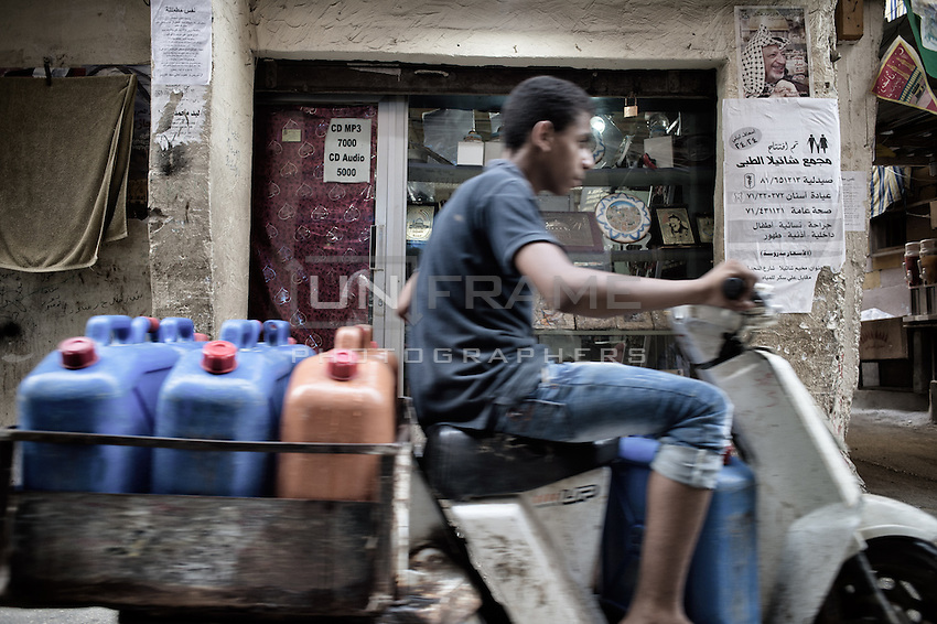 Water Delivery men driving scooter to the houses of the camp in Shatila. Beirut, Lebanon. August 2015