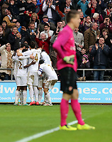 Sunday 06 January 2013<br /> Pictured: MIchu of Swansea is mobbed by team mates (L) celebrating his opening goal, whilst Wojciech Szczesny, goalkeaper of Arsenal stands dejected (R). <br /> Re: FA Cup third round, Swansea City FC v Arsenal at the Liberty Stadium, south Wales.