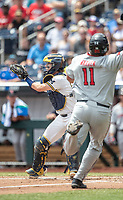 Michigan Wolverines catcher Joe Donovan (0) waits for a throw to the plate as baserunner Cameron Warren (11) slides home during Game 11 of the NCAA College World Series against the Texas Tech Red Raiders on June 21, 2019 at TD Ameritrade Park in Omaha, Nebraska. Michigan defeated Texas Tech 15-3 and is headed to the CWS Finals. (Andrew Woolley/Four Seam Images)