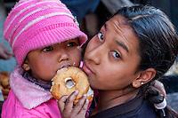 Bhaktapur, Nepal.  Mother with Little Girl Eating Doughnut.