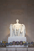Statue of Abraham Lincoln inside the Lincoln Memorial decorated with flowers for Presidents Day.