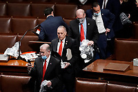 House of Representatives members leave the floor of the House chamber as protesters try to break into the chamber at the U.S. Capitol on Wednesday, Jan. 6, 2021, in Washington. (AP Photo/J. Scott Applewhite)