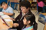 Afterschool homework help program for Headstart graduates Grades K-3 female teacher working with girl (second or third grader)