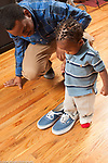17 month old toddler boy with father trying on his shoes
