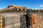 Morocco, High Atlas, Kasbah of Ait Ben Haddou: complex of traditional packed-earth buildings on UNESCO World Heritage List and location for more than 20 Hollywood film productions as Gladiator or Lawrence of Arabia - Carpet seller in traditional Berber dress selling carpets below the Kasbah of Ait Ben Haddou | Marokko, Hoher Atlas, Ait Ben Haddou: ein befestigtes Dorf (Ksar), das aus verschachtelten Kasbahs besteht, in traditioneller Lehmbauweise gebauten Wohnburgen, seit 1987 UNESCO Weltkulturerbe und Filmkulisse fuer mehr als 20 Hollywood Filmproduktionen wie Gladiator oder Lawrence of Arabia - ein Teppichverkaeufer in traditioneller Berber Kleidung