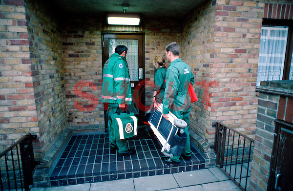 Paramedic ambulance crew rushing to an emergency call. They are waiting for someone to open the front door to allow them access to the patient...© SHOUT. THIS PICTURE MUST ONLY BE USED TO ILLUSTRATE THE EMERGENCY SERVICES IN A POSITIVE MANNER. CONTACT JOHN CALLAN. Exact date unknown.john@shoutpictures.com.www.shoutpictures.com....