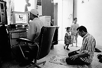 Iraq. Baghdad. Al Sadr City used to be called Saddam City. Moslem shiite family. A man sits by his desk and works on his computer, while another man is praying on his knees. The prayer uses a small carpet with a drawing of a mosque. A couple of children are also playing games in the room. © 2003 Didier Ruef