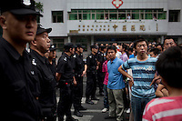 A Han Chinese crowd confront riot police after they arrested two Han men who were part of a mob that chased down a Uighur in Urumqi. They caught up with the Uighur and beat him before the police intervened firing shots in the air and arresting the two Han attackers. The mob then attacked the police to try and stop the arrests. Ethnic violence between the Uighur and Han people had erupted in the city a few days earlier.