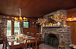 Onteora, New York. 1893: Aged, fir wainscoting and a beamed ceiling give the dining room a warm and inviting glow.  The room is centered on a stone fireplace which is decorated with a collection of tree fungi, some dating from the nineteenth century.