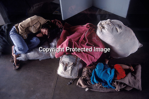 Homeless mother and family with possessions at bus station sleeping. Brasilia Brazil South America. 1980s  1985
