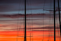 Sailboat masts and their rigging trace lines against a sunset sky of orange and gray clouds.