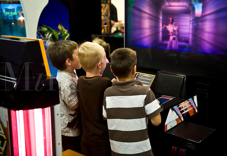 Boys playing a video game in an arcade.