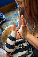 A mother breastfeeds her two year old daughter while doing a high five with her hand with him.<br /> <br /> Lancashire, England, UK<br /> <br /> Date Taken:<br /> 07-01-2015<br /> <br /> © Paul Carter / wdiip.co.uk