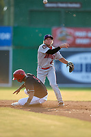 Auburn Doubledays second baseman Kyle Marinconz (4) turns a double play as Demetrius Sims (3) slides into second base during a game against the Batavia Muckdogs on June 28, 2018 at Dwyer Stadium in Batavia, New York.  Auburn defeated Batavia 14-9.  (Mike Janes/Four Seam Images)