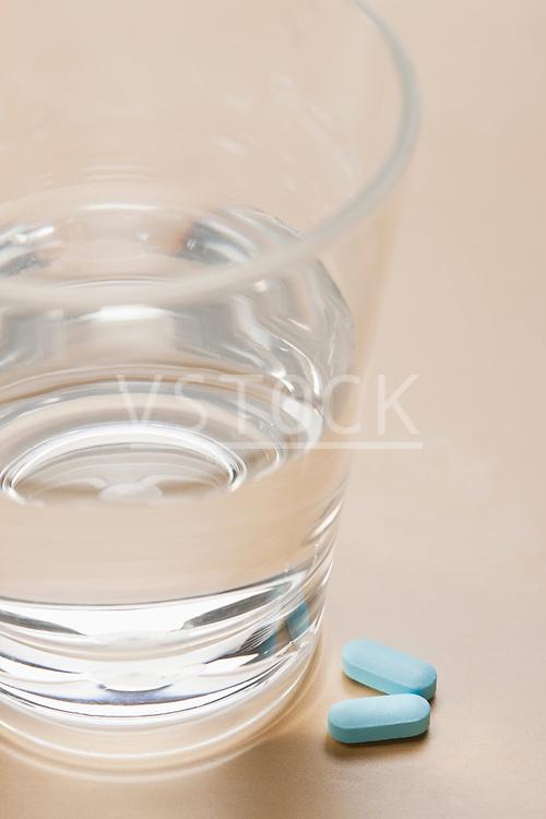 Pills near glass with water, studio shot