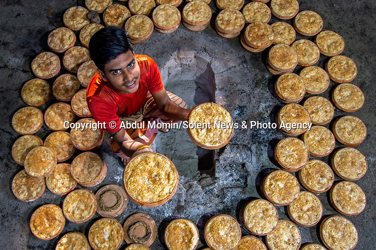 """Hundreds of clay pots are filled with curd as workers make the traditional dish in a Bangladeshi factory.  Photos taken in the country's largest curd making plant illustrate the process which sees 3,000 pots delivered in a day.<br /> <br /> The sweet dish, which is made by boiling milk to reduce it and mixing in yoghurt and sugar, is called 'Mishti Doi'.  Photographer Abdul Momin, who visited the factory in Sherpur Upazila to take these pictures, said: """"It is made by boiling the milk until it's reduced to half and thickened.  SEE OUR COPY FOR DETAILS.<br /> <br /> Please byline: Abdul Momin/Solent News<br /> <br /> © Abdul Momin/Solent News & Photo Agency<br /> UK +44 (0) 2380 458800"""