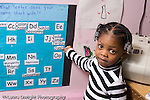 Education Preschool 3-4 year olds portrait of girl pointing with thumb to name on board of class names horizontal