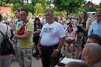 """Auf einer Buergerversammlung mit ca. 500 Teilnehmern im Berliner Plattenbaubezirk Hellersdorf entlud sich am Dienstag den 9. Juli 2013 der blanker Rassismus gegen eine geplante Unterkunft fuer syrische Buergerkriegsfluechlinge. Etwa 2/3 Anwesende aeusserten, es solle """"zuerst was fuer Deutsche getan werden"""", """"das Heim anzuenden"""", """"Wer sein Heimatland verlaesst ist ein Verraeter"""", """"Wer denkt an unsere Kinder"""" und aehnliche Parolen gegen das Fluechtlingsheim. Veranstaltungsteilnehmer, die Verstaendnis fuer die Buergerkriegsfluechtlinge aeusserten, wurden niedergebruellt.<br />Im Bild: Veranstaltungsteilnehmer mit T-Shirt mit dem Aufdruck """"Nein zum Heim"""", die von einer anonymen Buergerinitiative verteilt werden.<br />9.7.2013, Berlin<br />Copyright: Christian-Ditsch.de<br />[Inhaltsveraendernde Manipulation des Fotos nur nach ausdruecklicher Genehmigung des Fotografen. Vereinbarungen ueber Abtretung von Persoenlichkeitsrechten/Model Release der abgebildeten Person/Personen liegen nicht vor. NO MODEL RELEASE! Don't publish without copyright Christian-Ditsch.de, Veroeffentlichung nur mit Fotografennennung, sowie gegen Honorar, MwSt. und Beleg. Konto:, I N G - D i B a, IBAN DE58500105175400192269, BIC INGDDEFFXXX, Kontakt: post@christian-ditsch.de<br />Urhebervermerk wird gemaess Paragraph 13 UHG verlangt.]"""