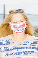 """A woman wears a facemask that says, """"Hello my name is Annoyed"""" as people gather for an anti-lockdown protest organized by the alt-right group Super Happy Fun America near the home of Massachusetts governor Charlie Baker in Swampscott, Massachusetts, on Sat., May 16, 2020. The protest was in defiance of Massachusetts orders mandating face coverings and social distancing and prohibiting gatherings larger than 10 people during the ongoing Coronavirus (COVID-19) global pandemic. The state's stay-at-home order is expected to be updated on May 18, 2020, with a phased reopening plan issued by the governor as COVID-19 cases continue to decrease. Anti-lockdown protests such as this have become a conservative cause and have been celebrated by US president Donald Trump. Many of the protestors displayed pro-Trump messages or wore Trump campaign hats and shirts with phrases including """"Trump 2020"""" and """"Keep America Great."""" Super Happy Fun America, organizers of the protest, are an alt-right organization best known for creating the 2019 Boston Straight Pride Parade."""