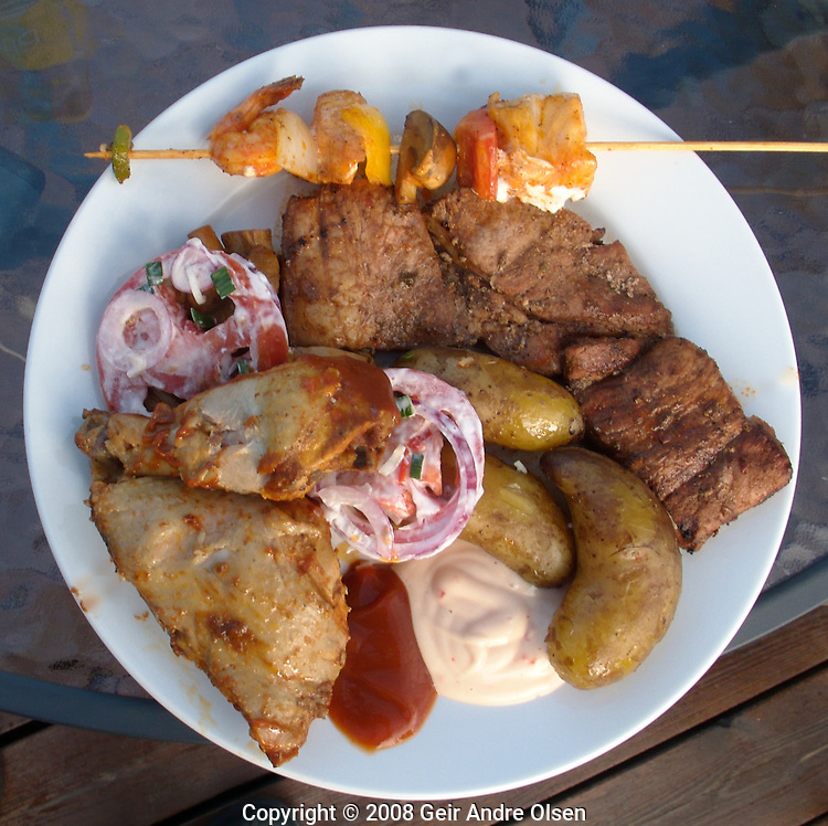 A barbecue plate with chicken, skewer, chop, salad and potato