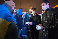 """Young people offering masks to everone on Square of Independence or """"Maidan Nezalezhnosti"""". Kiev. Ukraine. Thousands of people are continuing to express their support to european integration and protesting against decision of Ukrainian government to refuse signing of association with EU in Vilnius."""