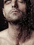 Sensual closeup portrait of a man face with closed eyes under pouring shower water Image © MaximImages, License at https://www.maximimages.com