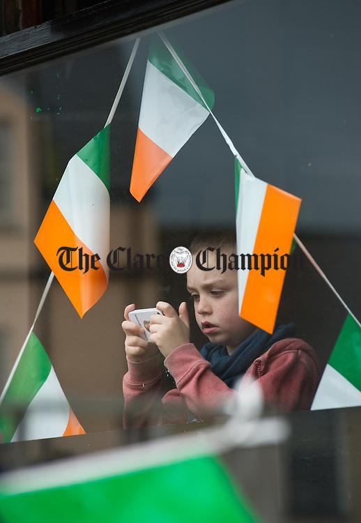 Bobby Jordan using his camera phone at the St Patrick's Day Parade at Sixmilebridge. Photograph by John Kelly.