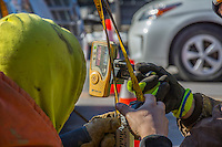 Workers use a laser transit to measure the depth of a hole a the State and Schrock road construction site.
