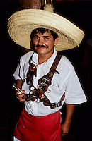 Mexican waiter with a big hat and a bullet belt with tequilla