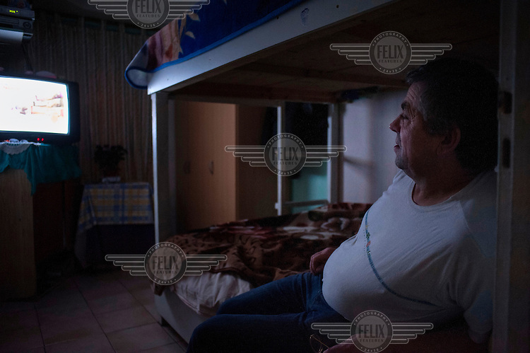 Mos Cotros, a construction worker from Romania, watches a Romanian news channel from his bed in his flat in St Denis on the outskirts of Paris.