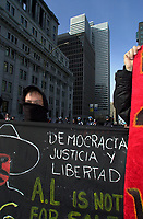 Montreal, April 17, 2001<br /> <br /> One  of demonstrators opposed to the Free Trade Area of the Americas (FTAA) raised a banner in spanish for Democracy, Justice and Liberty<br /> near the Police barricades <br /> on April 17, 2001 in downtown Montreal (Quebec, CANADA), near the and the Queen Elizabeth Hotel where the `` Conference of Montreal `` on economy globalization is beeing held until April 19th 2001.<br /> <br /> The  conference feature speakers such as Mexico President Foxx and New York Governor Pataki.<br /> <br /> Photo by Pierre Roussel /<br /> NOTE :  Uncorrected D-1 JPEG saved as Adobe RGB color space.