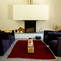 Two pairs of armchairs are grouped around the contemporary fireplace in the living room