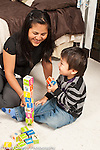 Two year old toddler boy with mother building with alphabet blocks giggling and playing